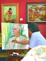 Master artist Yan Sun, native of China, paints a portrait of Marc Harshman at Centre Market. The original painting can be viewed in the Wheeling Room. (Photo by Linda Comins)