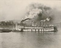 "The riverboat ""Valiant"" passing Wheeling Wharf. Notice that her smokestacks are down so that she could clear the bridges."
